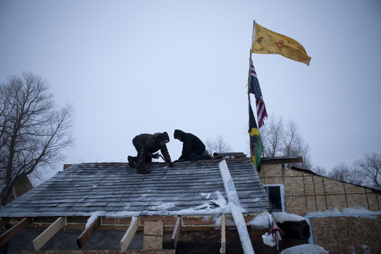 Brad Kallio and Linus Yellowhorse patch roofing on one of the many winter dwellings being constructed at the Oceti Sakowin Camp.