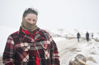 Crystal Houser of Oregon covers her face to stay warm at camp this winter. She encourages those around her to avoid conflict on a contentious bridge, where police and protesters have clashed in recent months.