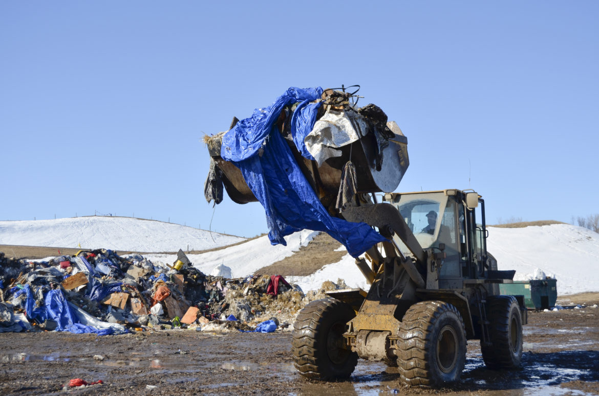 A front end loader picks up debris from camp before loading it on a semi to take it to a disposal site.