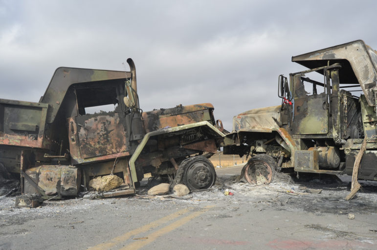 Protesters burned vehicles and left them on a state highway as a barricade to block out police from their camp during an October confrontation.