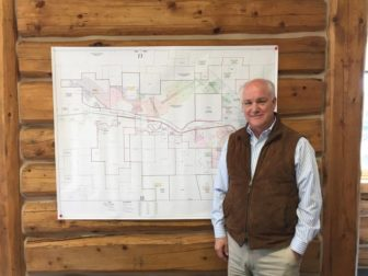 Randy Atkins standing in front of a layout of the Brook Mine in his Sheridan office