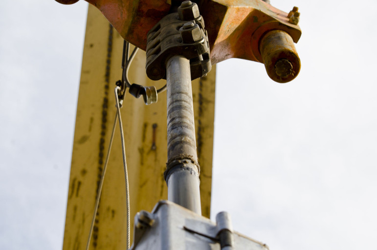 A steel spindle pumps oil on a farm in McKenzie County, North Dakota. Archeologists play a key role in the state's oil boom by surveying potential drilling sites on federal land.