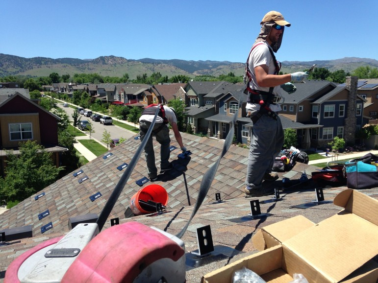 Employees with Namaste Solar install mounting brackets for a new rooftop system in Boulder, Colorado.