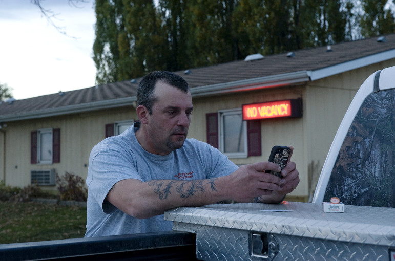 Bob Landerer, a crude oil truck driver from Pennsylvania now working in North Dakota, texting his wife back home. Landerer sleeps in his truck but showers and does laundry at the motel behind him. New Town, North Dakota.