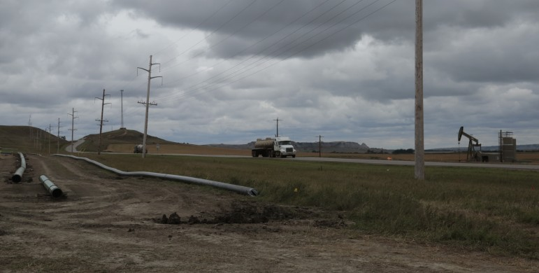 The story of North Dakota's flaring and crude by rail problems in one image: Natural gas flares from an oil well as an oil truck passes a site where a new pipeline is being laid.