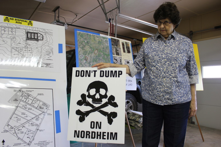 Lyn Janssen in her garage posing with her anti-waste pit posters