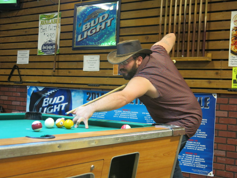 Energy worker Brandon Allee shoots pool at Jake's Tavern in Gillette, WY.