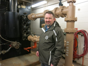 "Clint Bassett stands in front of two thick pipes labeled ""sludge in, sludge out."""