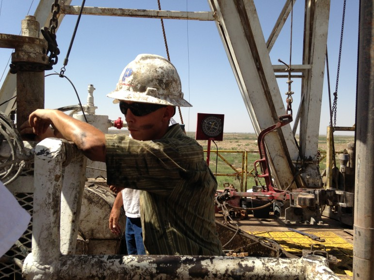 A young worker takes a short break atop a drilling rig outside Lovington, New Mexico.