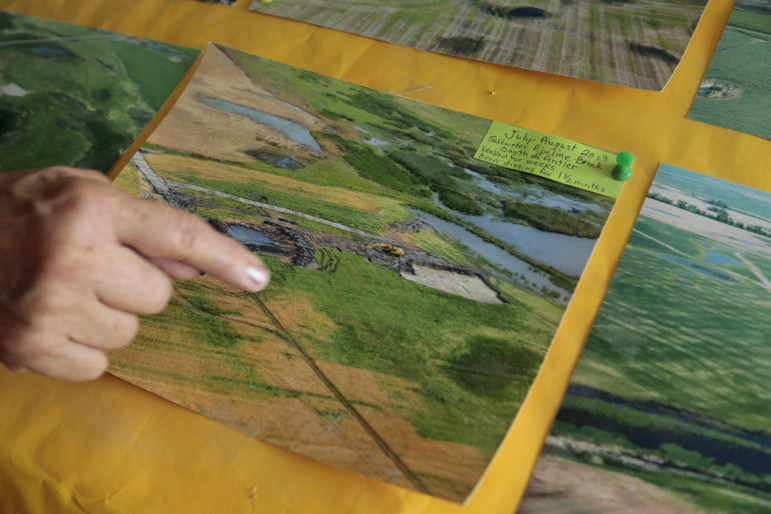 Christine Peterson points at an aerial photo of a wastewater spill near her land in Bottineau County, North Dakota.