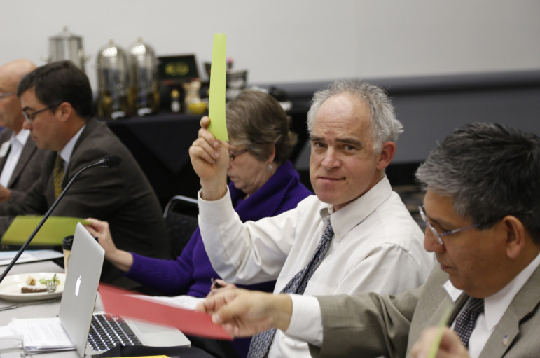 Task force member Will Toor holds up a green sheet to vote in favor of a policy recommendation during the group's February 3rd meeting.