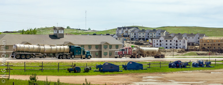 Oil trucks drive in front of new housing construction in Watford City, North Dakota.
