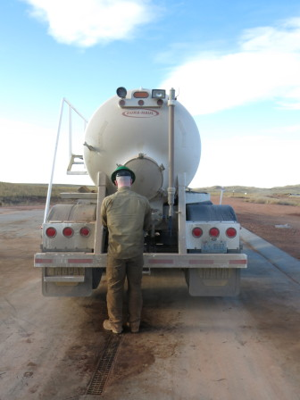 An employee of Black Bison Water Services prepares a truck to unload wastewater.