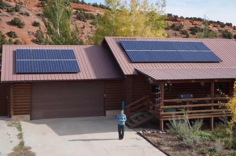 Holly Copeland in front of the family's house and their newly-installed solar array.