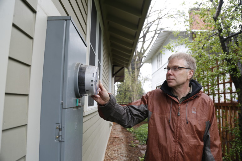 John Phelan with Fort Collins Utilities inspects the smart meter at his home.