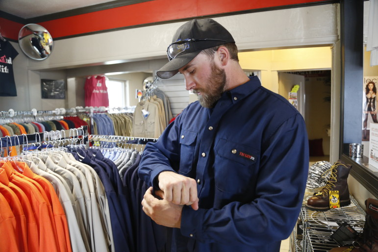 Will Kessler, a welder working in Colorado's oil fields, tries on a flame resistant shirt at Frackin' Hot FR in Greeley, CO.