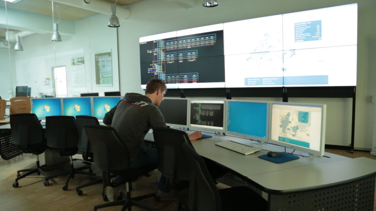 Graduate student Alexander Hermann pulls up power flow diagrams for the Danish island of Bornholm in the grid control room at PowerLabDK
