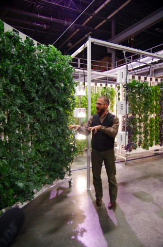 Bright Agrotech CEO Nate Storey demonstrates how indoor, vertical farming works in the company's Laramie warehouse.