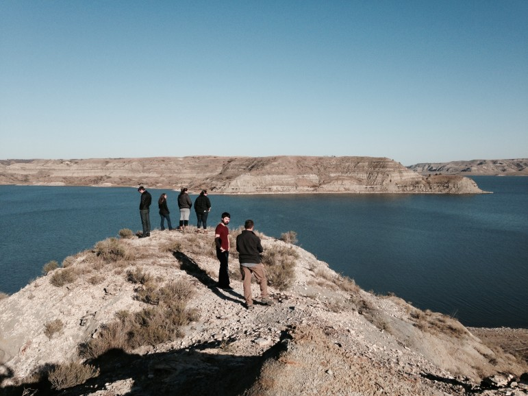 The University of Colorado Team stands with Prairie Rose Seminole on a bluff overlooking Lake Sakakawea, observing native plants and the changing landscape.