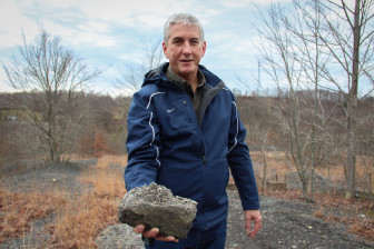 Eric Cavazza, director of Pennsylvania's Bureau of Abandoned Mine Reclamation, holds up some coal refuse from the waste pile in Fredericktown.