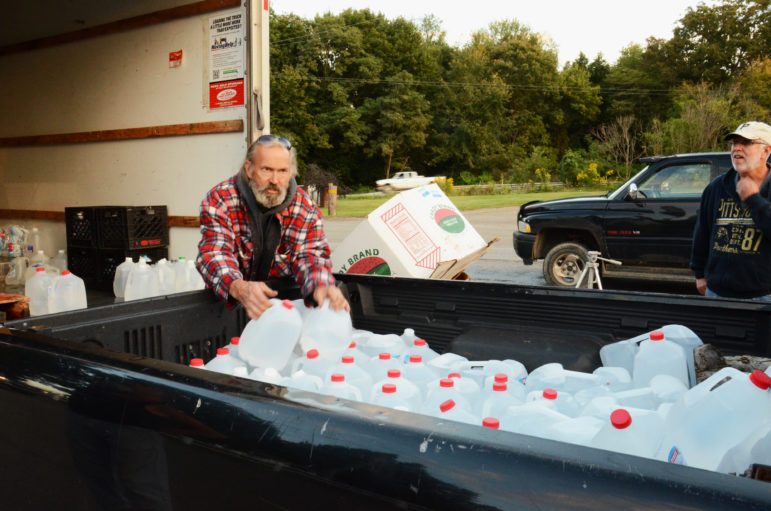 Fred McIntyre loads donated drinking water into a resident's truck in Connoquenessing Township.