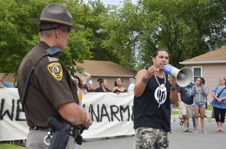 Dallas Goldtooth of the Indigenous Environmental Network voices his opposition to the Dakota Access Pipeline while law enforcement monitors the protest on the street in front of the North Dakota Capitol. Highway Patrol Capt. Bryan Niewind offered him a megaphone to amplify his voice.
