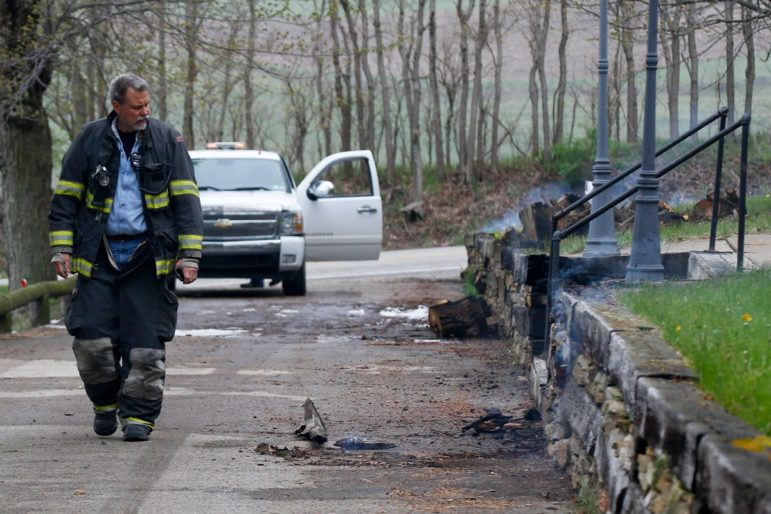 A first responder walks by smoldering wood and a burning retaining wall near a home following a natural gas explosion at a pipeline complex, on Friday, April 29, 2016, in Salem Township, Pa. The explosion caused flames to shoot above nearby treetops in the largely rural area, about 30 miles east of Pittsburgh, and prompted authorities to evacuate businesses nearby.