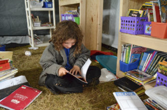 Kai Knott, 9, flips through a book in the literacy room of the school at camp. The makeshift school is contained in several large tents for now, but those in charge of the facility plan to build a more permanent structure to endure the winter.