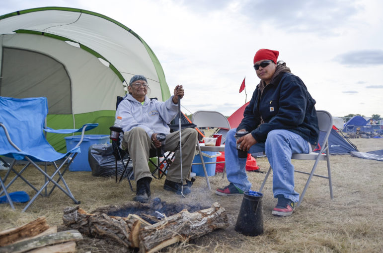 Quiltman Sahme, left, and son Tiwani sit outside their tent along the border of the Standing Rock Sioux Reservation in North Dakota where they're protesting the Dakota Access oil pipeline. They're from the Warm Springs Indian Reservation in Oregon, which is trying to prevent Nestle from bottling water from a nearby stream.