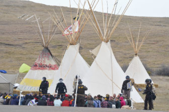 Police guard protesters arrested for refusing to leave a camp on private land along the Dakota Access pipeline route.